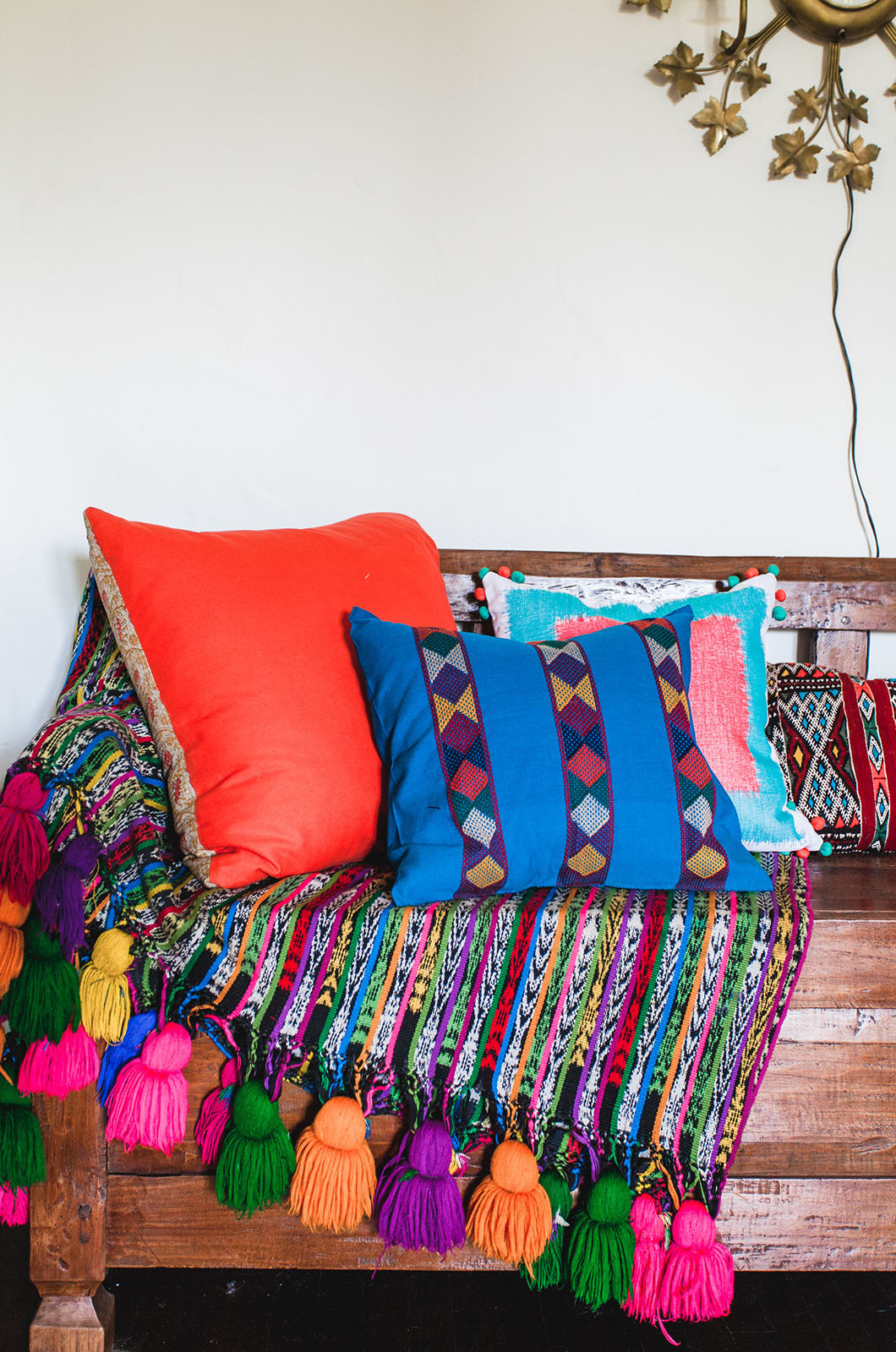 Vintage blankets and pillows are casually displayed atop an Indonesian wooden bench in the living room.