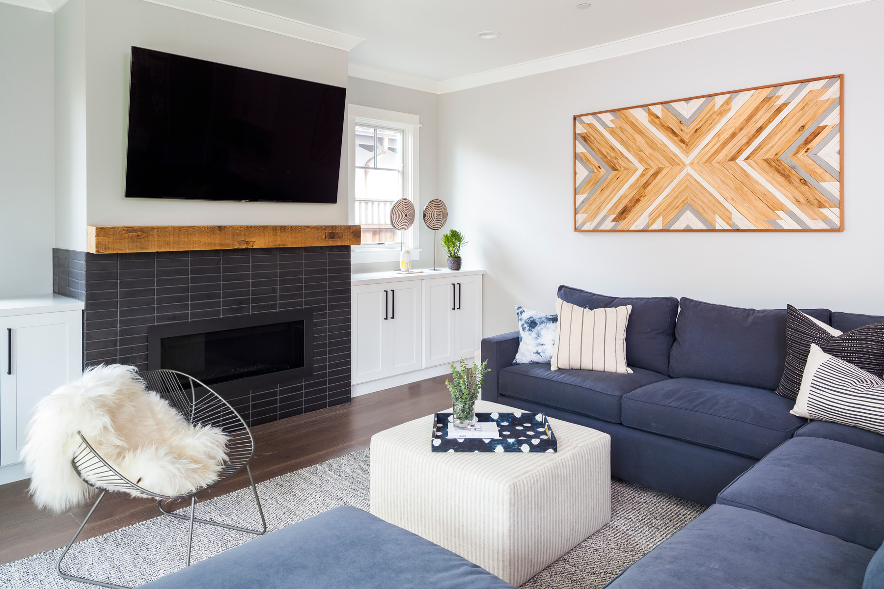 A custom-tiled fireplace is a great spot for the family to gather. The space also features a standout art piece by woodworker Alexsandra Zee.