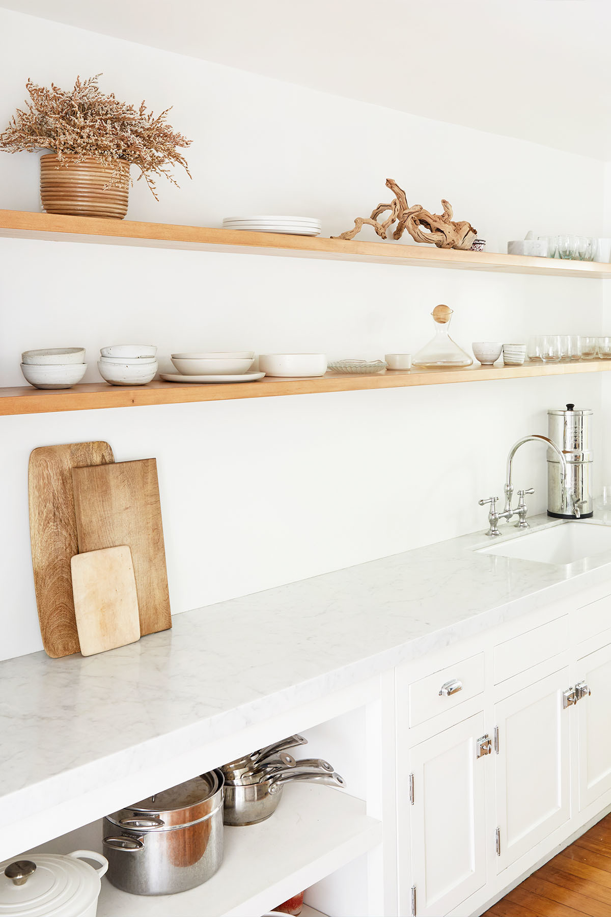 Deters keeps her kitchen space ultimately pared-back, with uniform ceramics and textured pieces from her favorite home stores. Food52 Glassware | Food52 Boards | Rachel Saunders Ceramics | Mud Ceramics | Gjusta Goods Ceramics | Le Creuset Dutch Oven | Custom Carrara Counter | Custom Floating Shelves | Original Cabinetry.