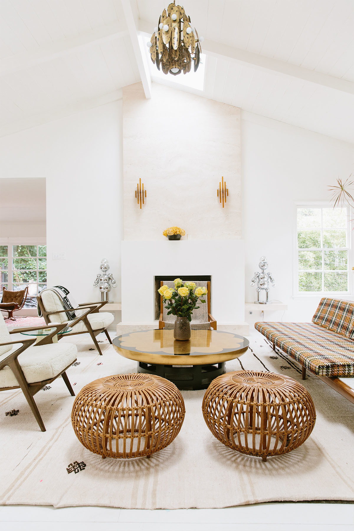 Eclectic vintage furniture is given a whole new lease of life inside the Sanders' Beverly Hills home. Lawrence of La Brea Rug | Vintage Italian 1970s' Robot Lamps, Set of Two | 1stdibs Sconce Lights | Chairs, Coffee Table, couple's own design | Vintage Sofa, Ottomans, Vase.