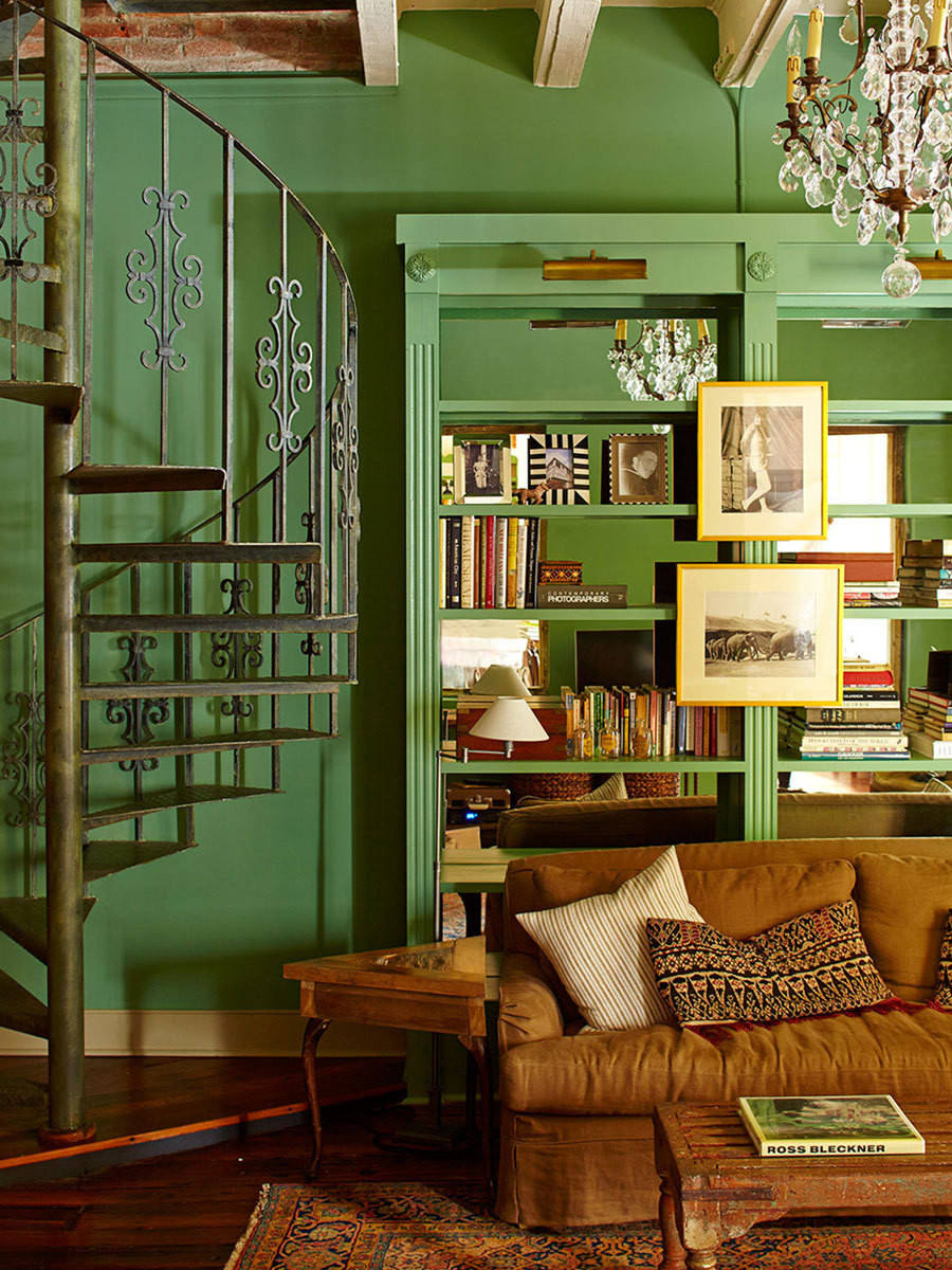 Mirror-backed bookshelves and a spiral staircase in the living room.