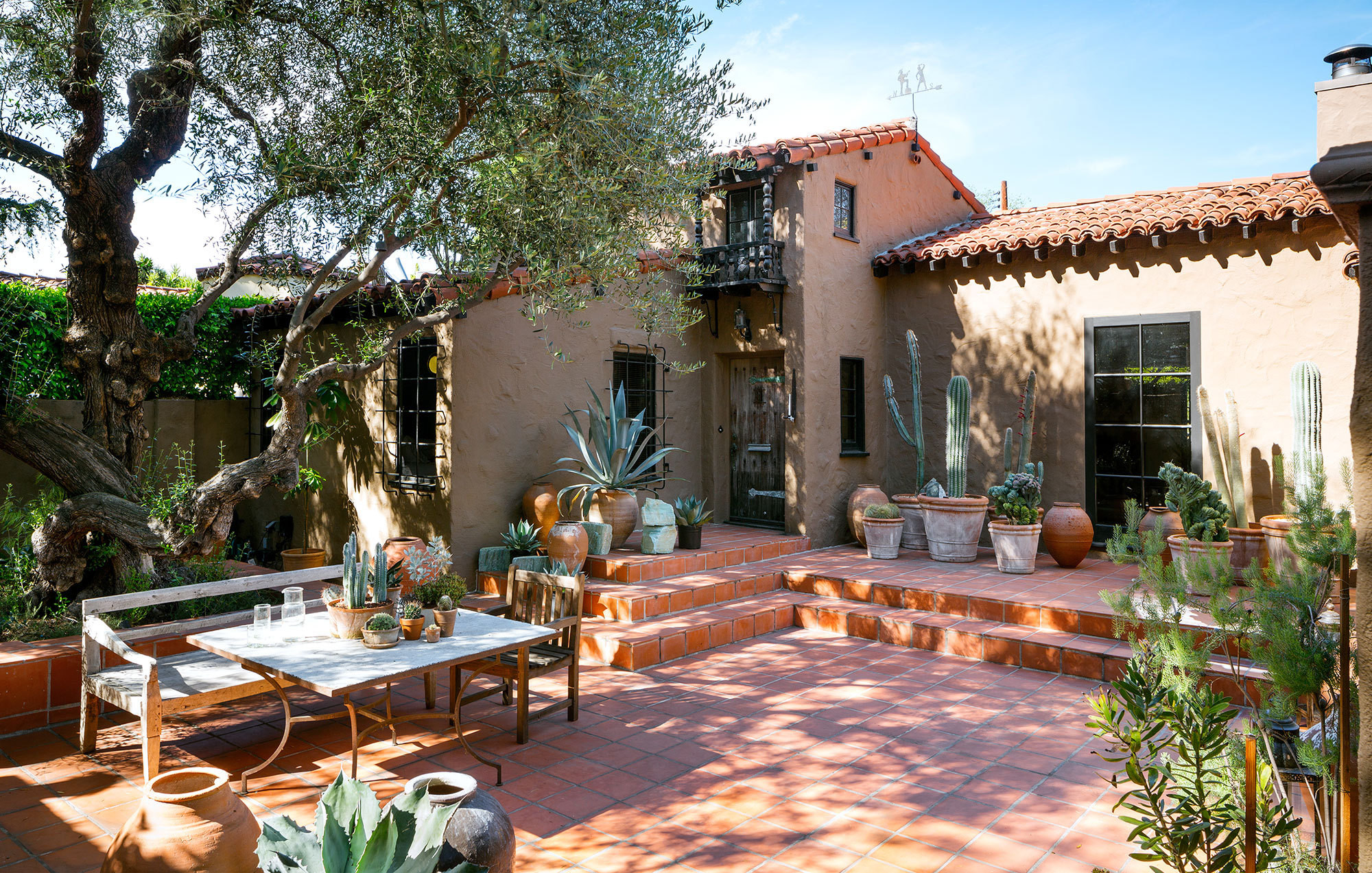 Container gardens of cacti (designed by Duncan) look right at home in the red-tiled outdoor living room.