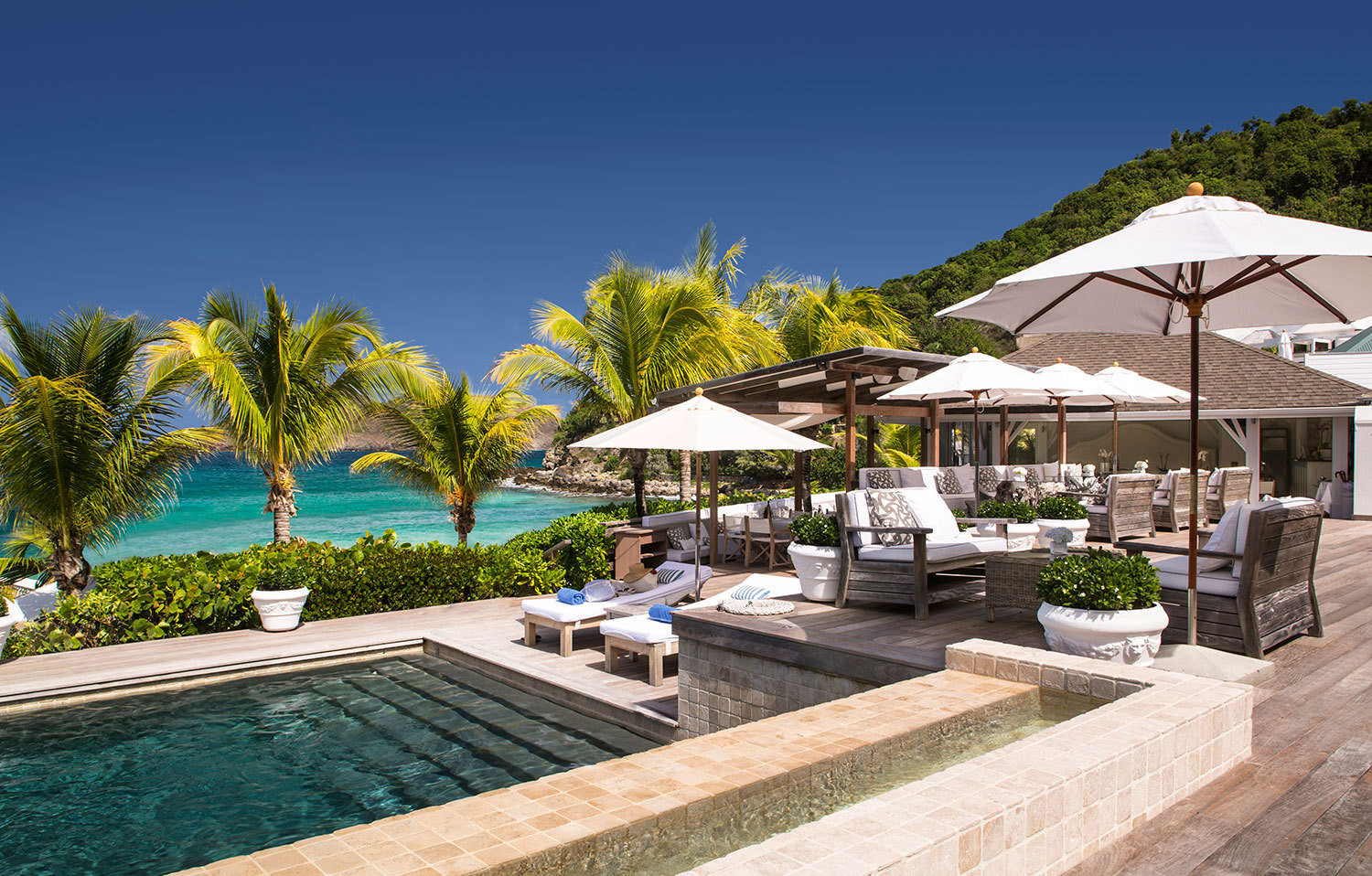 At Cheval Blanc St-Barth Isle de France white-cushioned deck furniture surrounds a lagoon-green pool that sits above the bay.