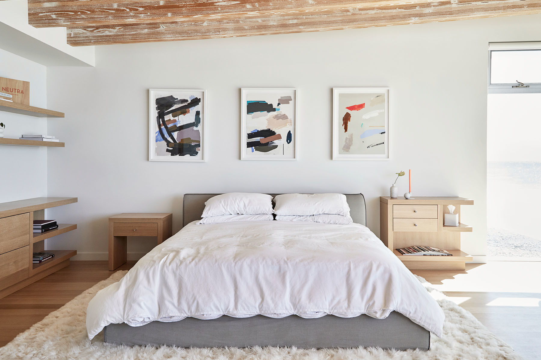 The master bedroom features a king-sized, custom bed, and opens up on to a breathtaking balcony. Custom Bed | Custom Shelving | Restoration Hardware Bedding | Maaari Ceramics | Karina Bania Artwork via Uprise Art.