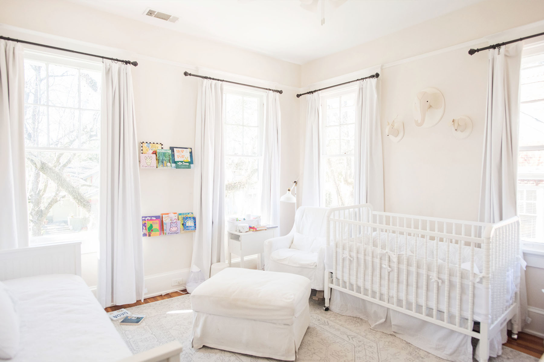 Baby Tempe's crisp, white nursery, provides ample room for play and cozy bedtime stories. Target Crib | Restoration Hardware Armchair | IKEA Ottoman | Restoration Hardware Animal Heads | IKEA Shelves | IKEA Lamp | Restoration Hardware Drapes | Wayfair Bedding.