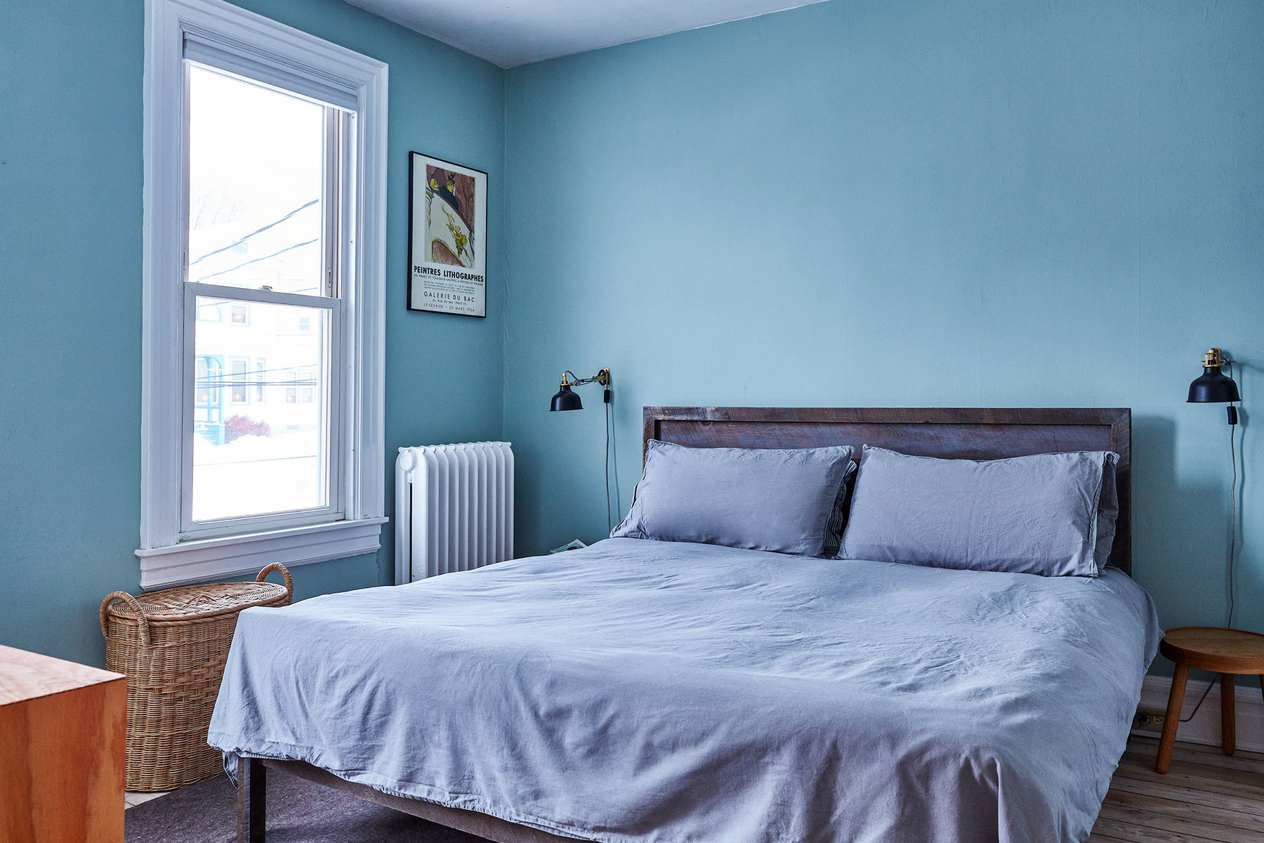 Blue walls and dove blue linen drive the Scandinavian aesthetic in the couple's guest bedroom. Benjamin Moore Paint | Chad Silver Design Bed | IKEA Sconce Lights | IKEA Bed Linen | IKEA Customized Dresser | Vintage Artwork | Vintage Rug | Chad Silver Design Stool.