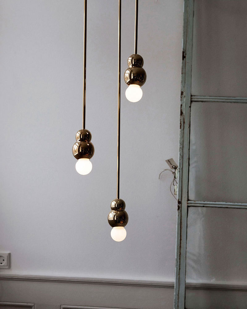 A trio of brass pendant lamps on display at the Apartment.
