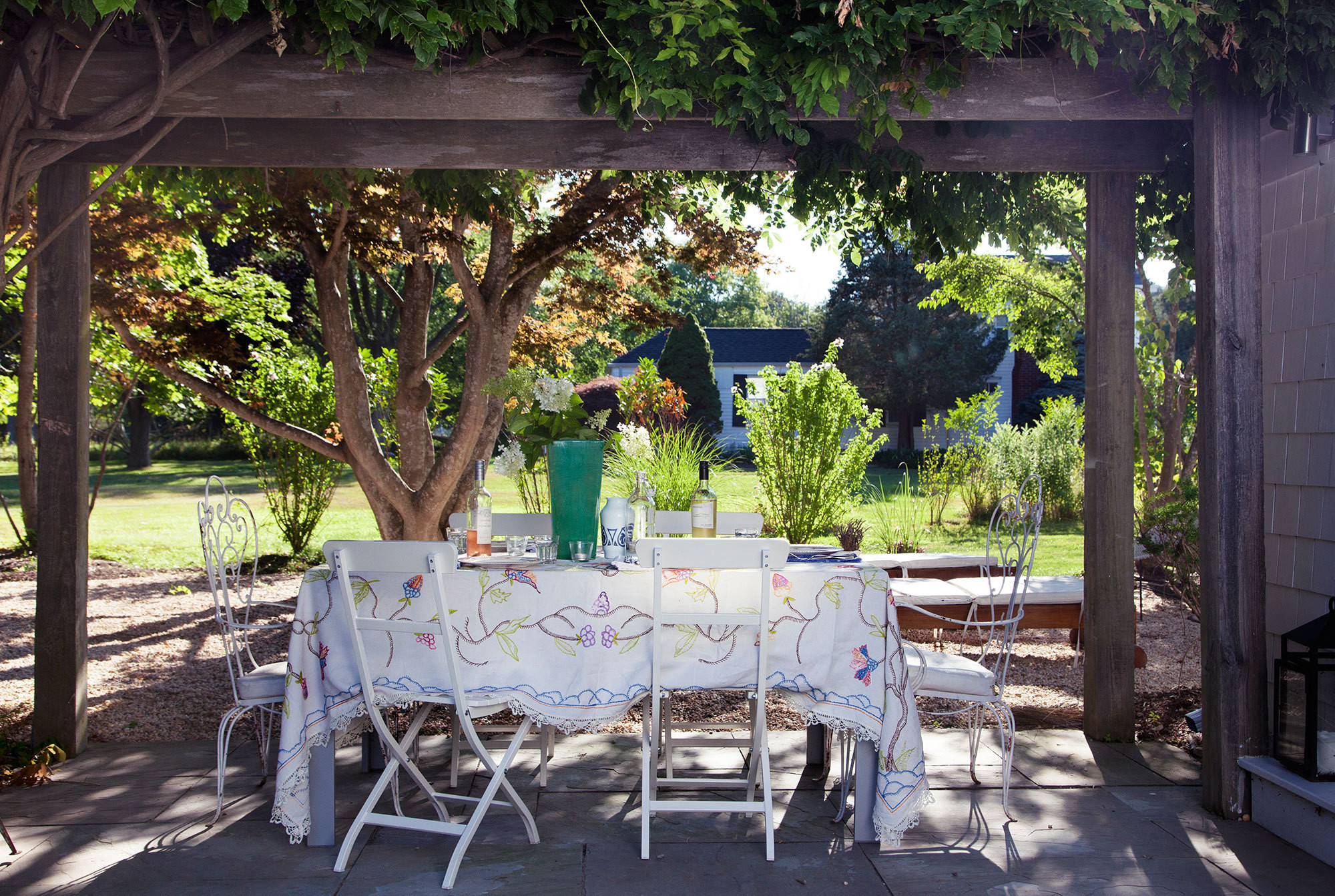 A trellis covered in wisteria vines provides a shady spot for casual meals outdoors.