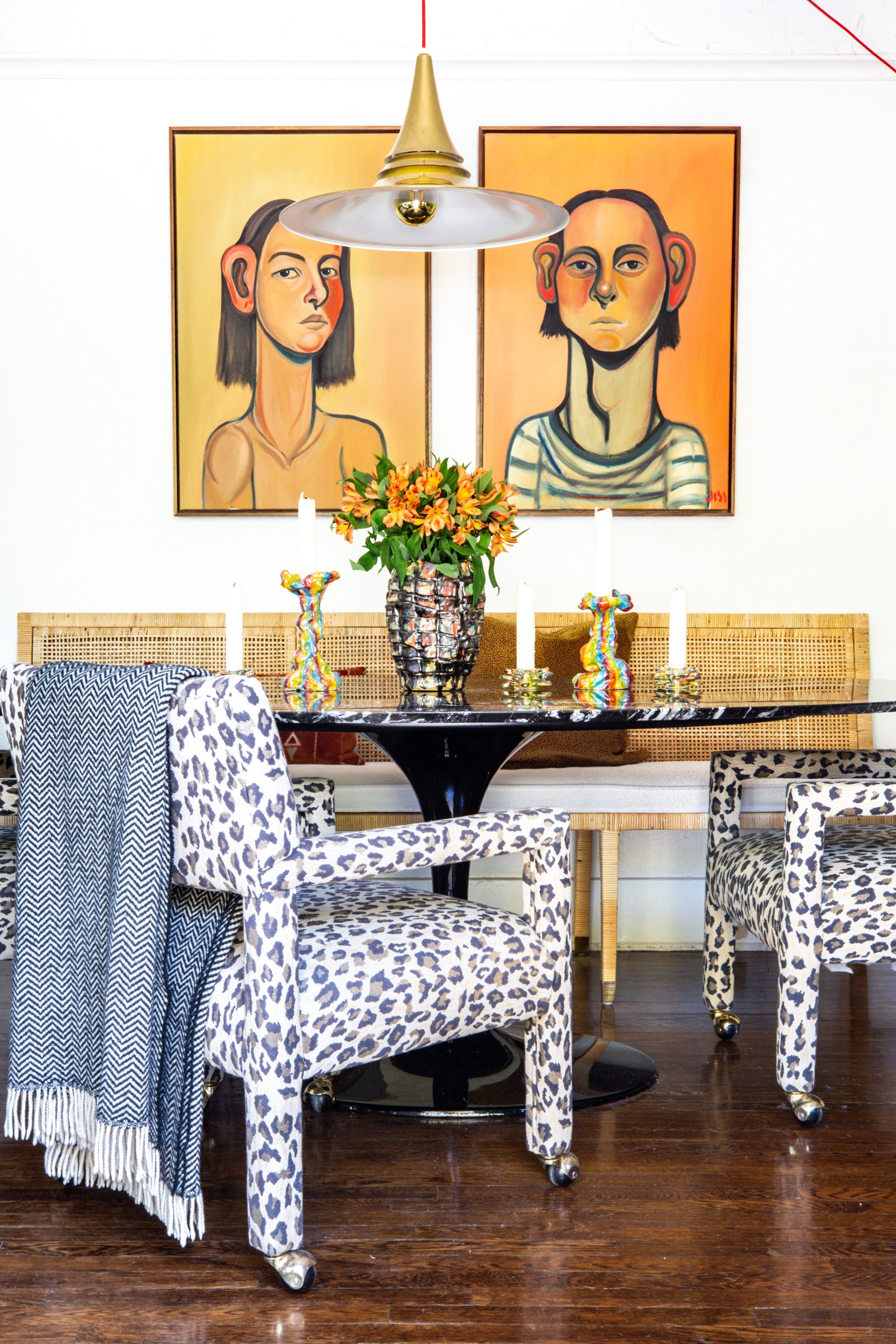 A stylish clash of pattern and color is on bold display at the dining table.Serena & Lily Bench |Missoni Throw |Saarinen Dining Table |Milo Baughman Style Dining Chairs |VintagePendant Light |Jackie Rines Vase |Jackie Rines Candle Holders |Jess Valice Portraits