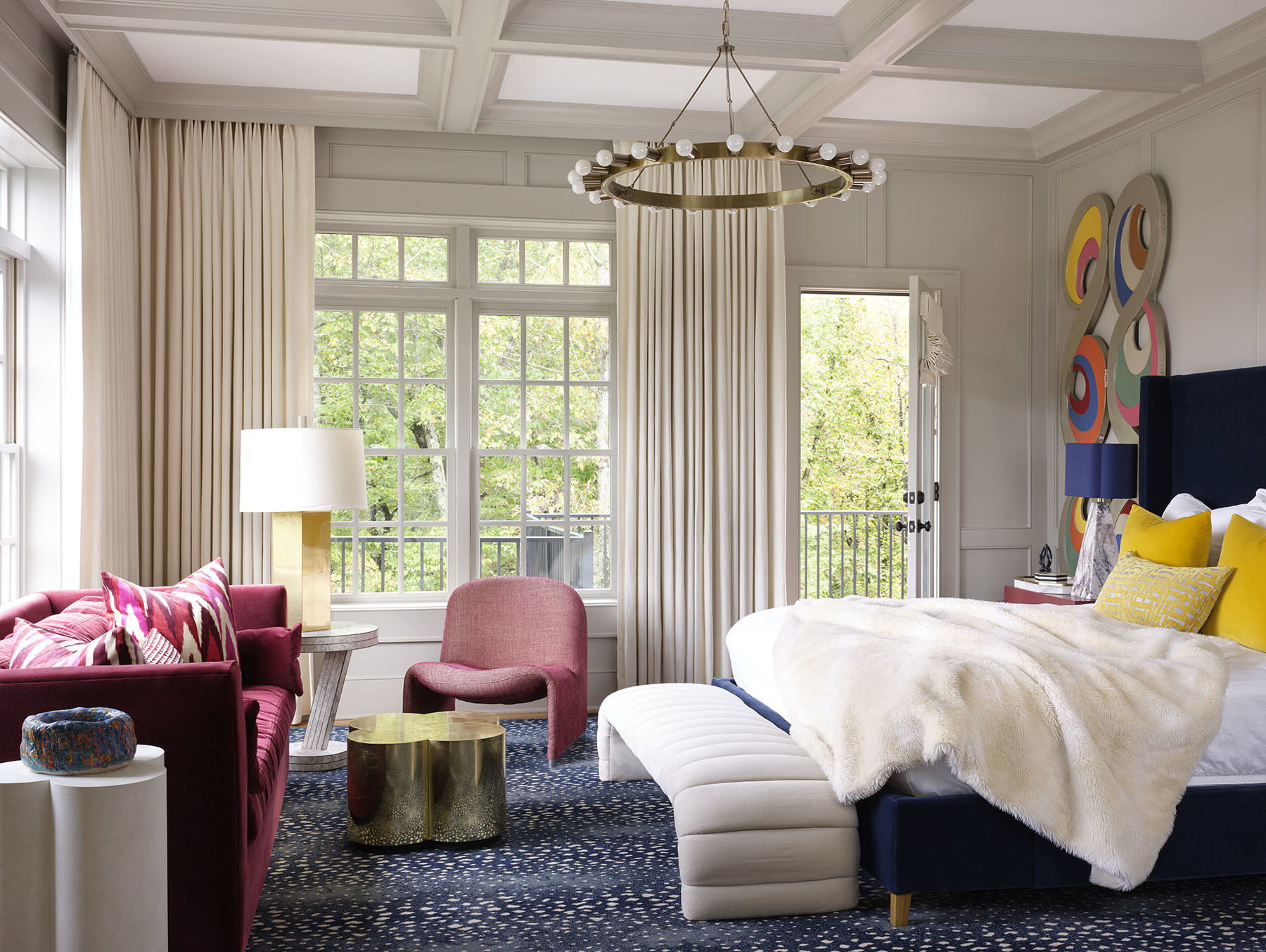 Varying shapes, texture, and color come together in the master bedroom to really showcase Blehm's signature playful aesthetic. Restoration Hardware Bed | Restoration Hardware Bedding | Flor Area Rug | Vintage Bench Seat | Restoration Hardware Sofa | Gillian Bryce Nesting Table | Clayton Gray Home Chandelier | Vintage Armchair | Custom Drapes