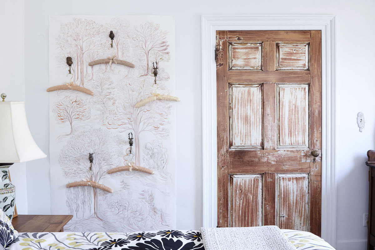 In a guest bedroom, Moylan hand-painted a wall with a woodsy scene and installed fauna-themed hooks for hangers.