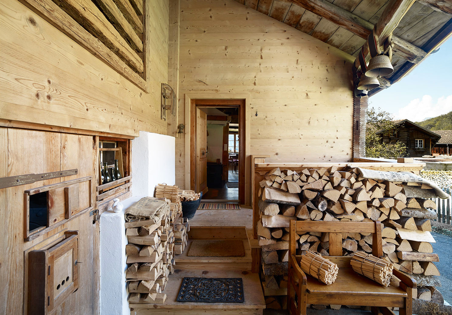 Stacks and bundles of wood, as well as traditional cowbells, welcome visitors to Patrick Schaffter and Werner Jahnel's chalet in Switzerland's Bernese Oberland.