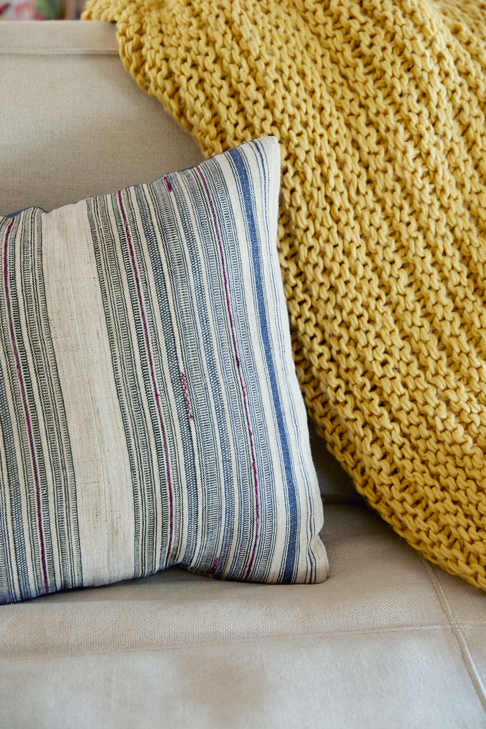 A muted striped pillow and saffron throw from West Elm add contrast and texture to the neutral sofa.