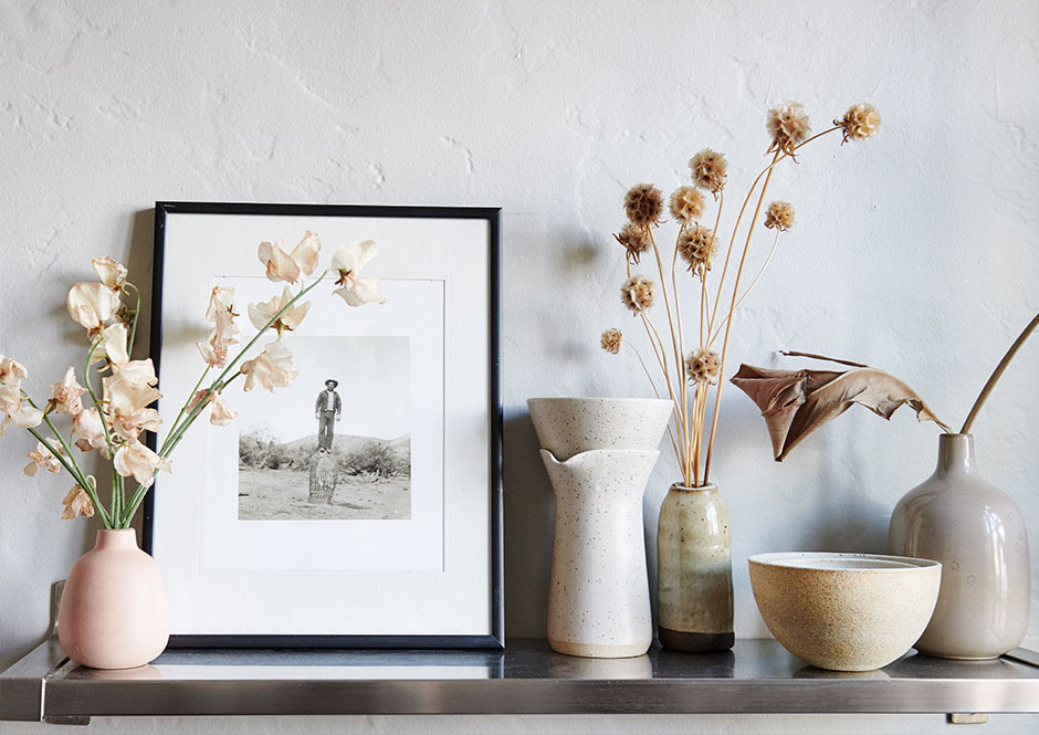 Personal touches — like cuttings from the Marigold workshop and a vintage photograph of Andrés' great-grandfather taken in Patagonia — decorate the open shelves throughout the duo's apartment. Heath Ceramics, Julie Cloutier Ceramics Assorted Vases.