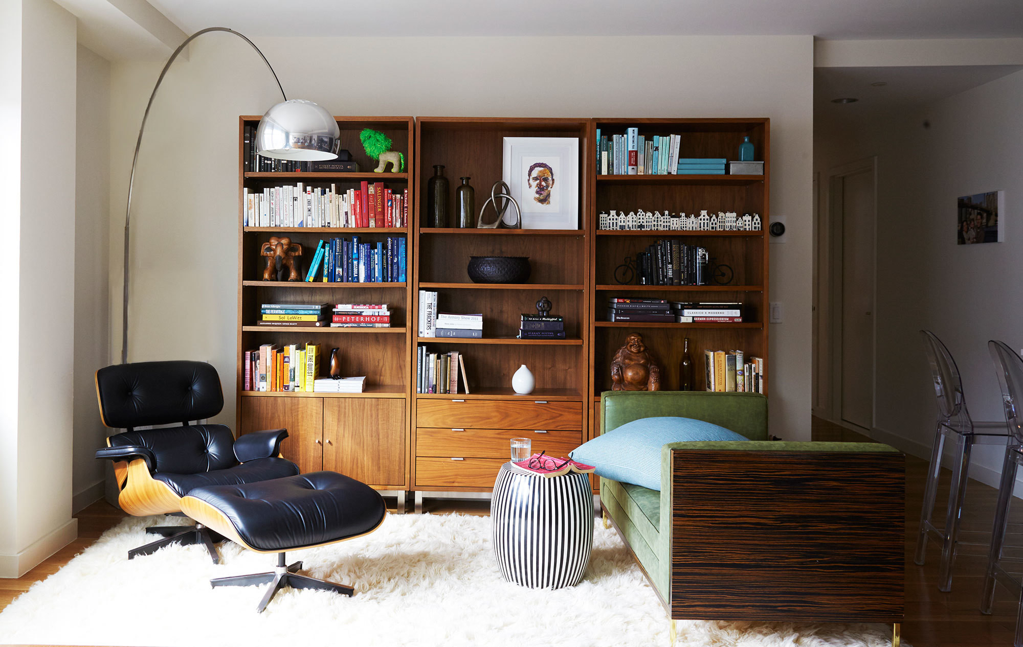 A classic Eames lounge and vinyl-upholstered daybed are complemented by a punchy, striped garden stool and color-coded bookshelves.