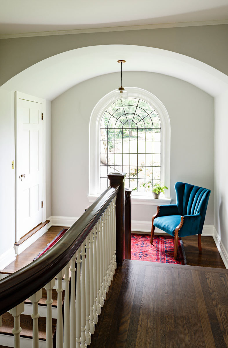 A round-top window turns the second-floor landing into a luminous reading nook.