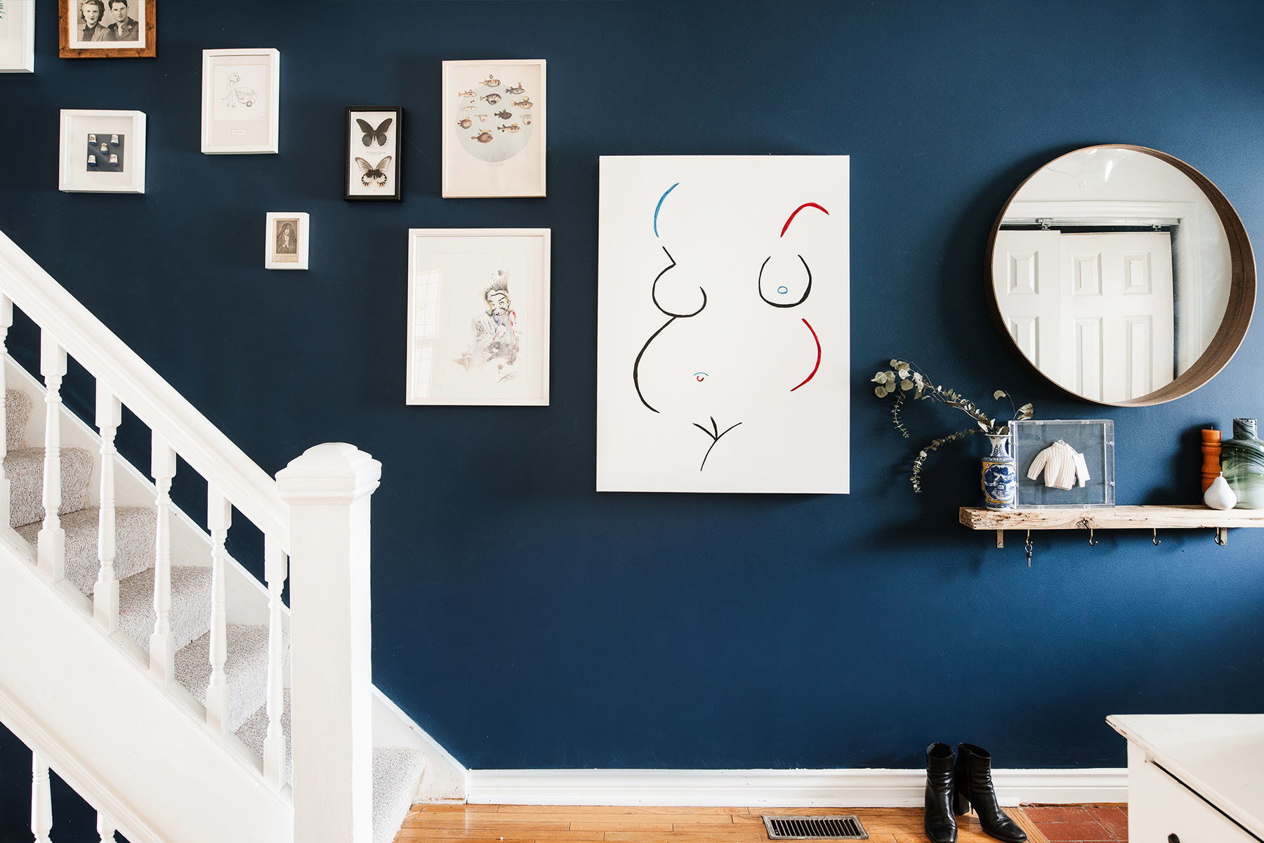 The couple's stairway boasts an eclectic look and feel, showcasing vintage family photos and sourced treasures. Behr Paint | IKEA Mirror | Custom Shelf | Ralph Damman Torso Artwork | Ryan Dineen Fish Print | State Goods Butterflies Print | Lee Kurn Lion Print | Ryan Dineen Watercolor | Umbria Cashmere Council Plaque.