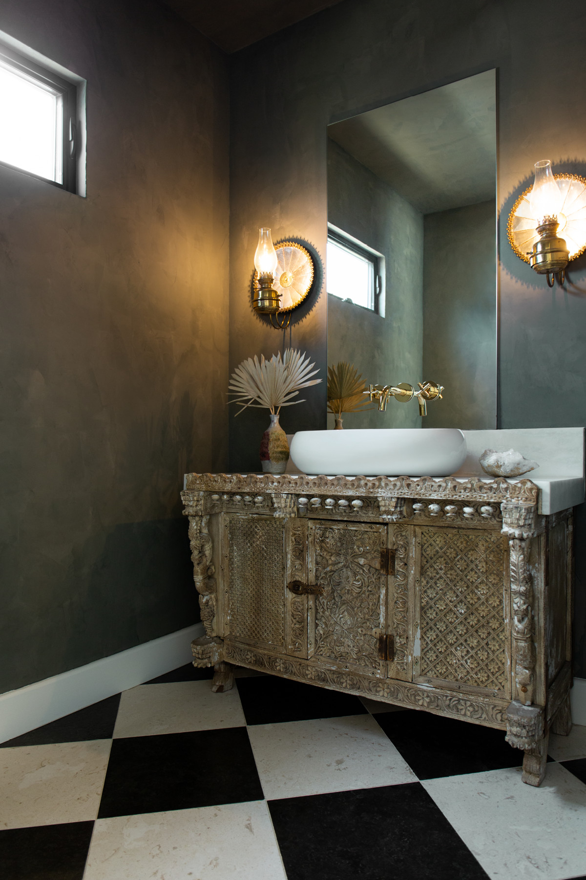 With a checkered limestone floor and moody palette, the powder room is the home's hidden gem.Portola Paints & Glazes Paint | Vintage Vanity | Vintage Sconces.