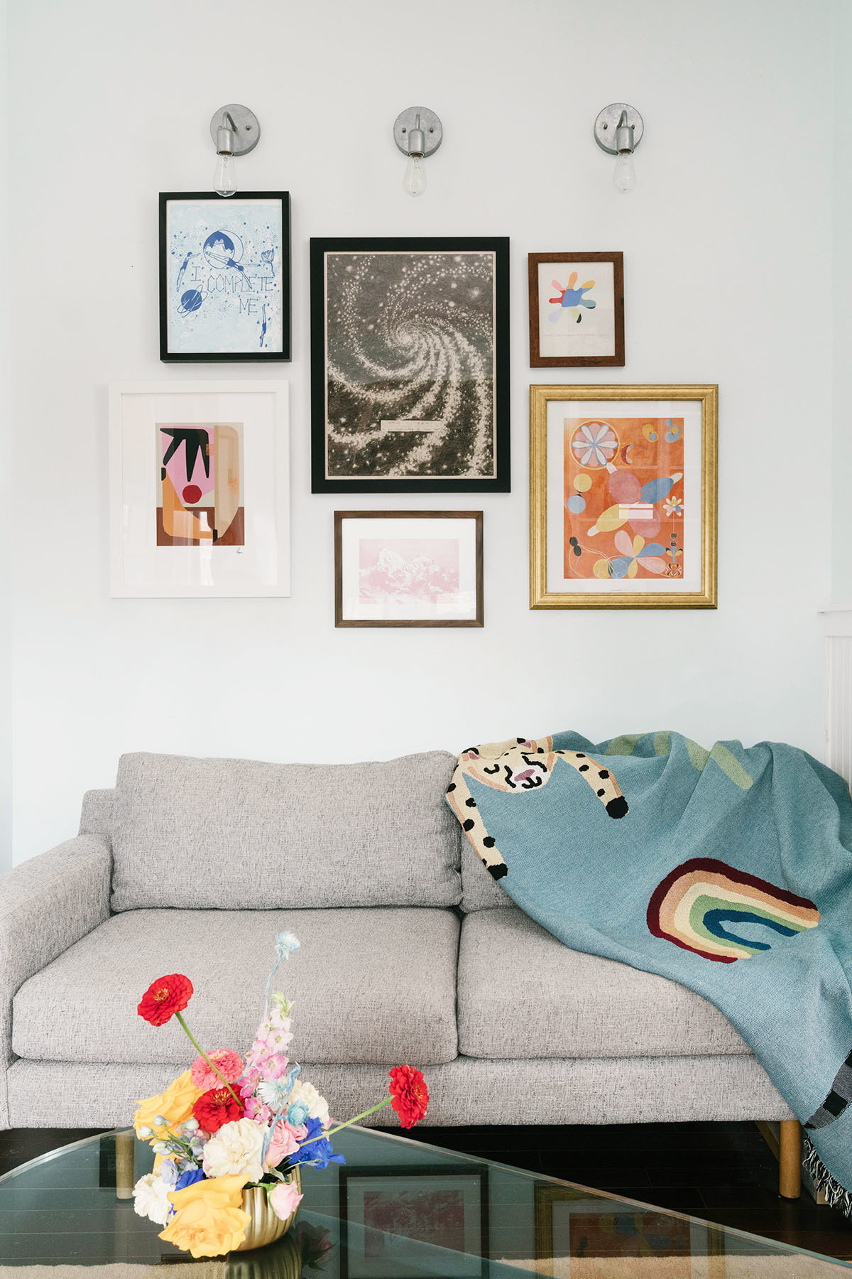 A makeshift gallery wall — complete with unique works of art and pieces Li's acquired over time — hold pride of place in the living room. West Elm Love Seat | Jarmel for Urban Outfitters Throw | Noguchi Coffee Table | Cold Picnic Rug | Lindsay Arakawa Print | Guggenheim Poster | Easy Does It Artwork | Jamali Garden Vase.