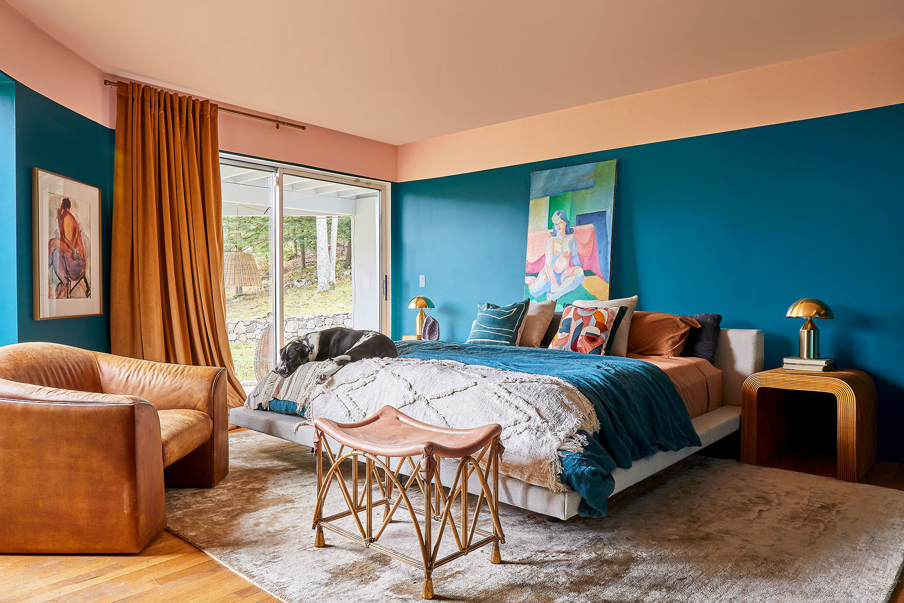 A punchy palette of teal and burnt orange complete the main bedroom space. Benjamin Moore Paint | Patina, Etsy, Assorted Pillows | Brimfield Leather Armchair | DeSede Vintage Armchair | Wayfair Rug | Spacio Terrano Bench Seat | Overstock Drapes | AllModern Table Lamps.