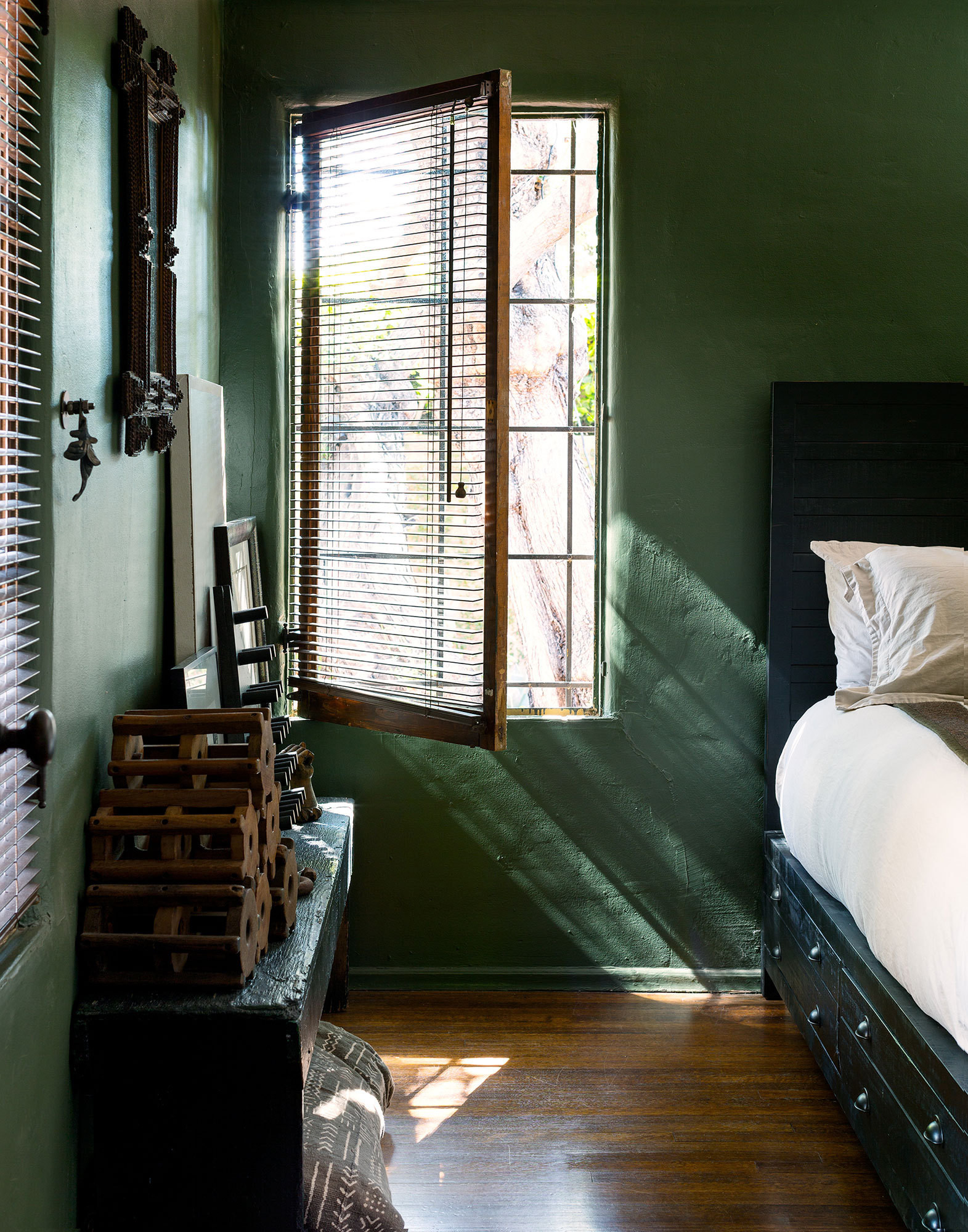 The master bedroom is painted in a soft forest green.