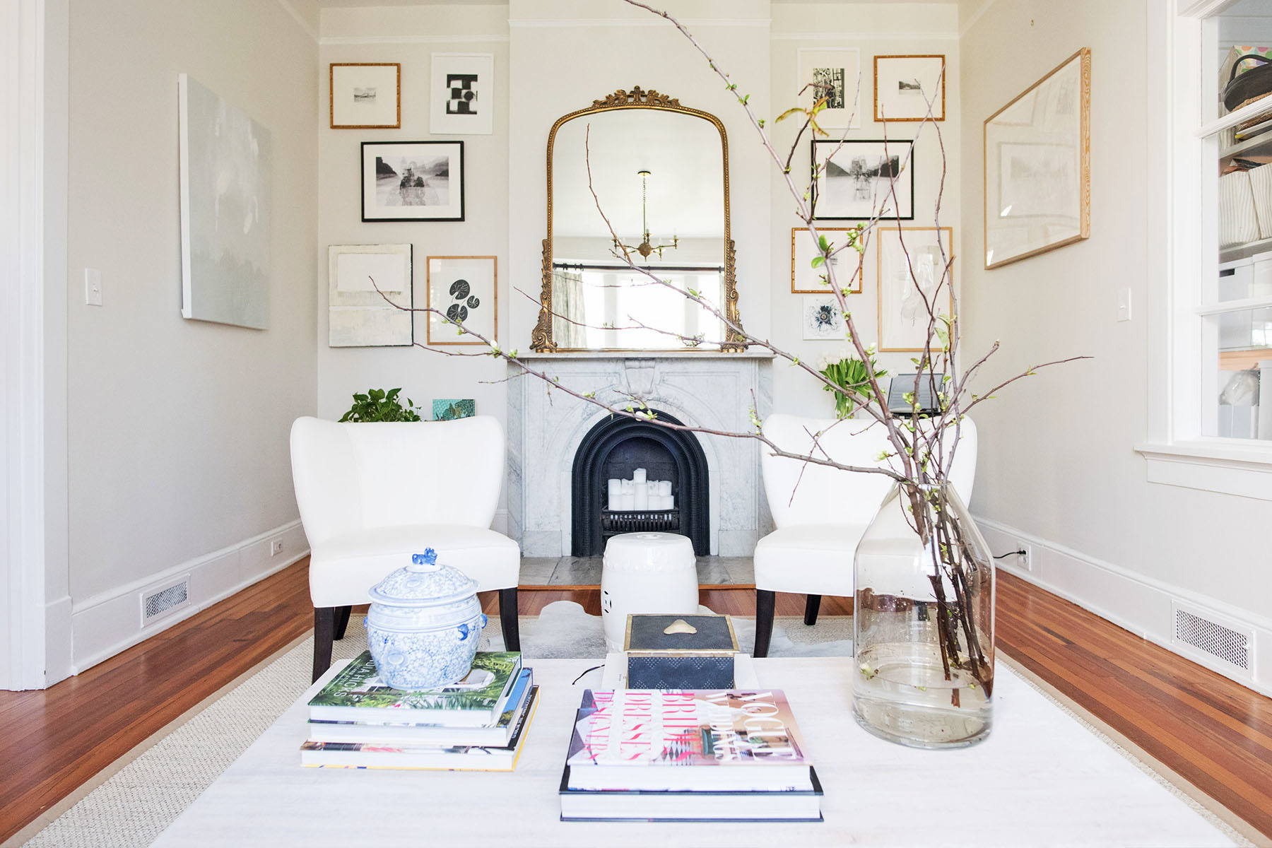 The family's sitting room harks back to its history. Anthropologie Mirror | Scott Antique Market Armchairs, upholstered in Schumacher Linen | Wayfair Stool | Target Vase | Homegoods Assorted Picture Frames.